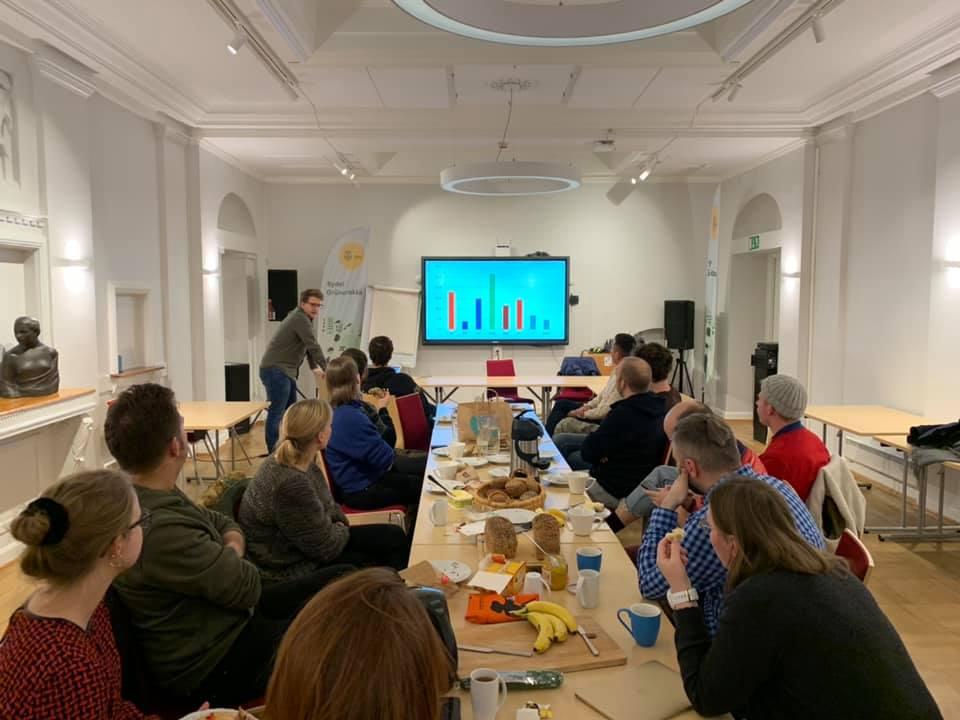 Mennesker rundt langbord lytter til presentasjon