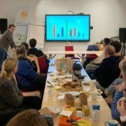 Mennesker som sitter rundt et langbord, lytter til presentasjon.